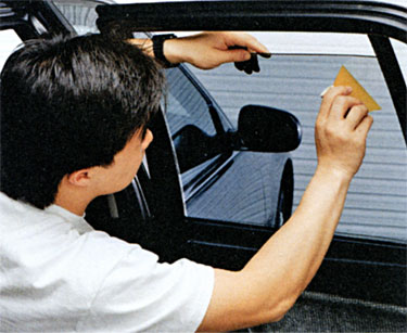 Applying window tinting film to car window.